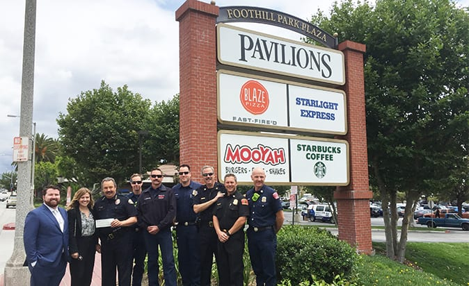 Members from the Monrovia Police Department and Firefighters Association gather in front of Foothill Park Plaza to accept donation from Westar Associates.
